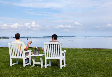 patio chairs: Two senior people in patio chairs drinking champagne by Chesapeake bay