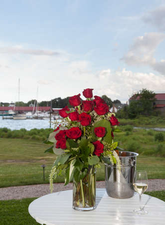 Bunch of red roses in vase on patio table with white wine in harbor setting