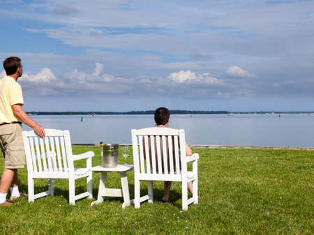 Two senior people in patio chairs drinking champagne by Chesapeake bay photo