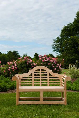 garden furniture: Teak carved bench on lawn by flower bed with rose bushes Stock Photo