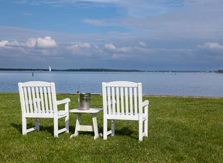 Empty patio chairs by side of the Chesapeake bay overlooking St Michaels harbor photo