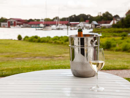 Chilled ice bucket with champagne bottle and glass in front of St Michaels harbor