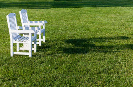 Empty patio chairs sitting on grass lawn in late afternoon sunshine photo