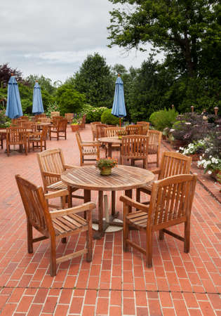 Many wooden teak tables and chairs on brick pation in cafe or restaurant photo