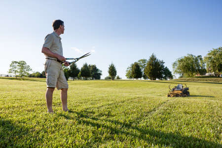 mowing grass: Challenging task of cutting large lawn with grass shears by hand with mower in background