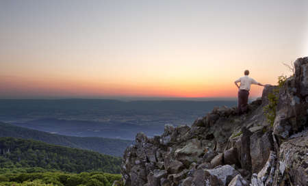 stony: Back view of man watching sunset from rocky summit of Stony Man on Skyline Drive in Virginia