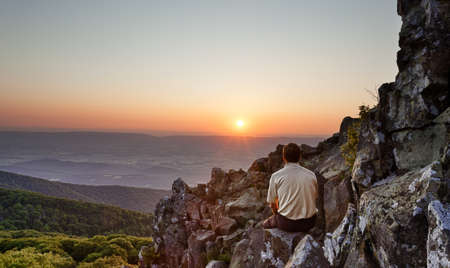 Blue Ridge Mountains: Back view of man watching sunset from rocky summit of Stony Man on Skyline Drive in Virginia