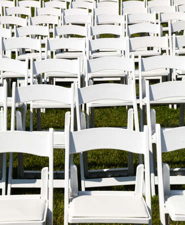 wedding chairs: Rows of formal white wooden wedding chairs set up for a wedding or concert