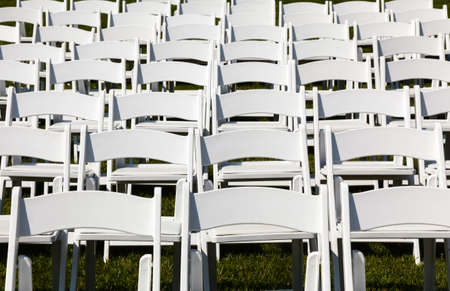 Rows of formal white wooden wedding chairs set up for a wedding or concert photo