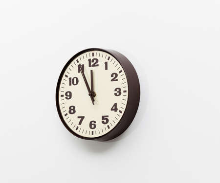 Brown simple plastic wall clock on the wall of office and concept of running out of time photo