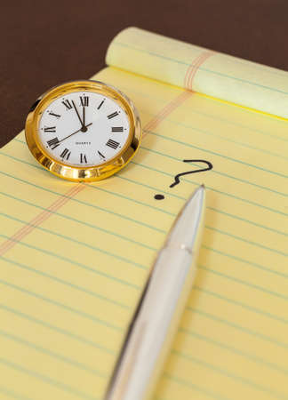 Concept for urgent decision making with clock on paper and question mark on pad photo