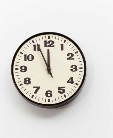 running out of time: Brown simple plastic wall clock on the wall of office and concept of running out of time Stock Photo