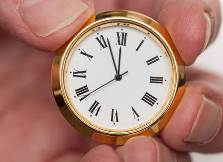 Small gold colored clock almost at midnight held by tips of fingers Stock Photo - 14212156