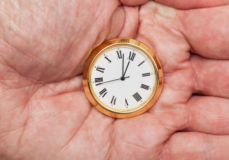 Small gold colored clock almost at midnight held in palm of hand Stock Photo - 14212162