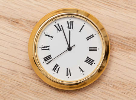 Small gold colored clock almost at midnight and laying on a wooden table photo