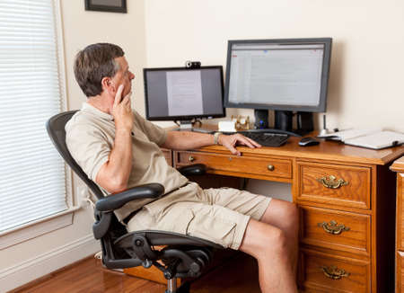 home office desk: Senior caucasian man working from home in shorts with desk with two monitors Stock Photo