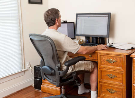 Senior caucasian man working from home in shorts with desk with two monitors photo