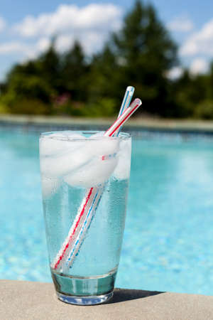 Plain glass of water with ice cubes on side of blue swimming pool photo