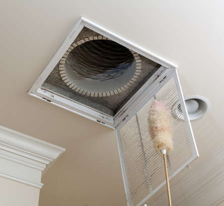 Dusting the vent for air conditioning filter in ceiling of modern home