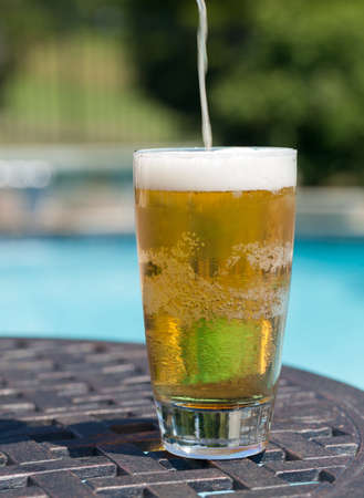 pint glass: Plain pint glass of beer being poured sitting on table by blue swimming pool