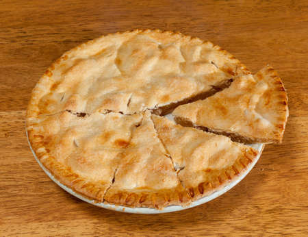 Freshly baked hot apple pie on wooden table Stock Photo