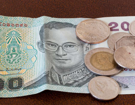 baht: Twenty baht note from Thailand with miscellaneous coins Stock Photo