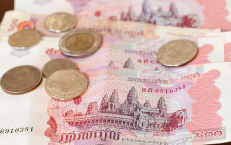 riel: Five hundred riel notes from Cambodia with coins from Thailand Stock Photo