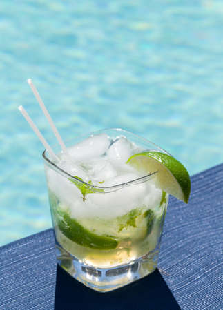 Glass of ice cold majito in glass by side of swimming pool photo