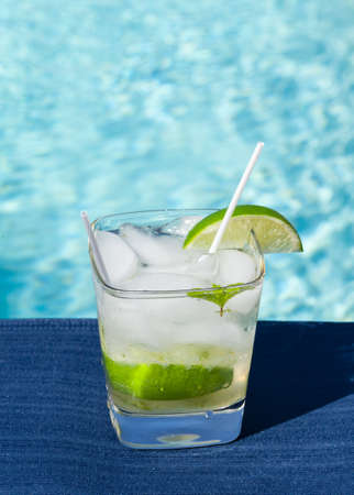 bacardi: Glass of ice cold majito in glass by side of swimming pool