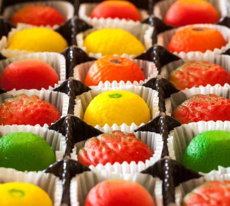 marzipan: Fruit shaped candies in macro image of marzipan sweets in paper wrappings Stock Photo