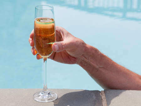 Elegant flute glass of sparkling white wine or champagne being held from in pool Stock Photo - 14341111