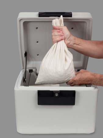 cash box: Fire proof safe open and large cotton cash bag being placed inside