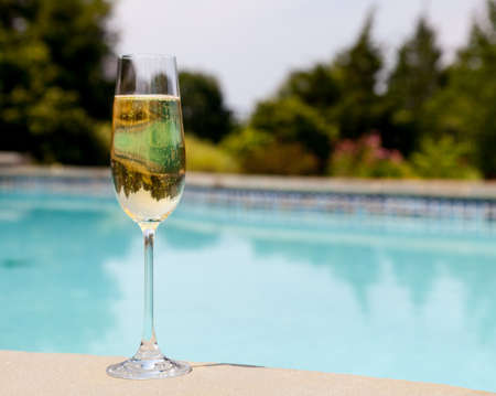 Elegant flute glass of sparkling white wine or champagne by side of swimming pool photo