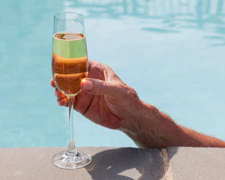 Elegant flute glass of sparkling white wine or champagne being held from in pool Stock Photo - 14341115