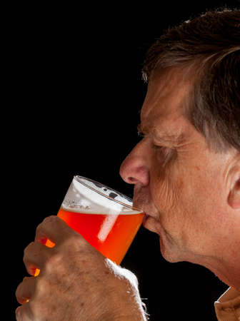 pint glass: Senior caucasian man in profile drinking from a pint glass of beer or lager