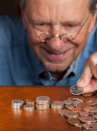 maniacal: Senior retired caucasian man counting out cash into piles