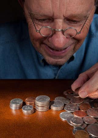 monedas antiguas: Mayor jubilado caucásico contando dinero en pilas