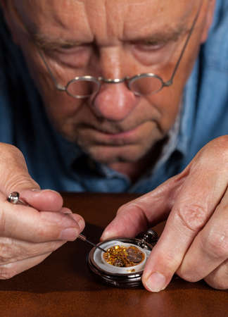 Senior caucasian repairman working on an old pocket watch photo