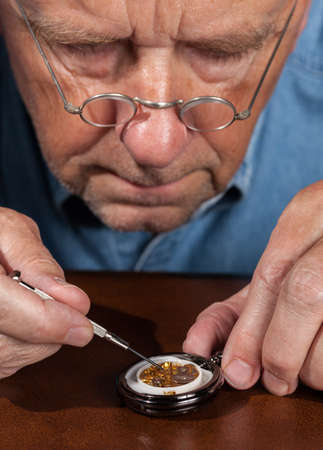 watchmaker: Senior caucasian repairman working on an old pocket watch