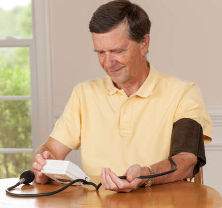 Senior caucasian retired male taking blood pressure at home photo