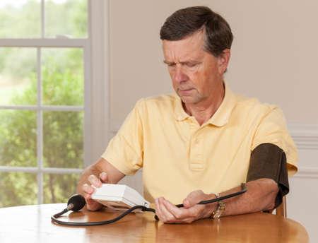 hipertension: Principal cauc�sico hombre retir� la presi�n de extracci�n de sangre en su casa Foto de archivo
