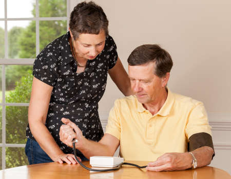 old man on a physical pressure: Senior caucasian retired male taking blood pressure at home
