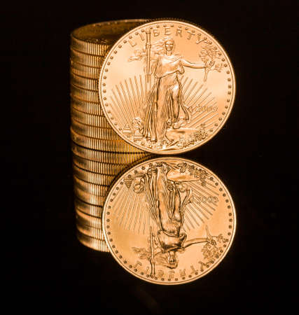 gold coin: Reflection of single gold coin and stack on black polished surface