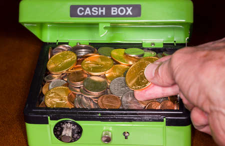 secure: Green cash box with combination lock open to show piles of coins including gold and silver