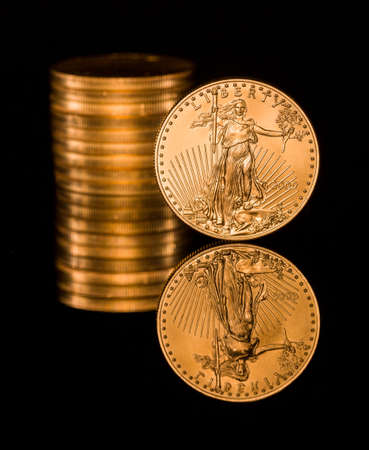 Reflection of single gold coin and stack on black polished surface Stock Photo - 14474715