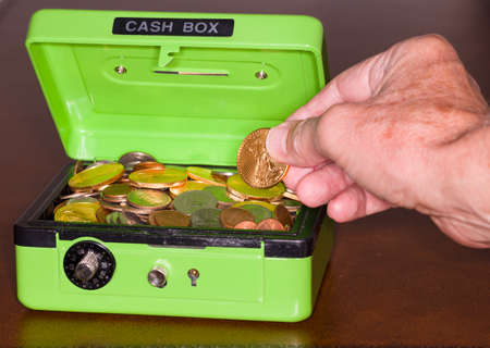 Green cash box with combination lock open to show piles of coins including gold and silver photo