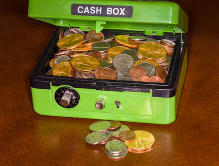 Green cash box with combination lock open to show piles of coins including gold and silver
