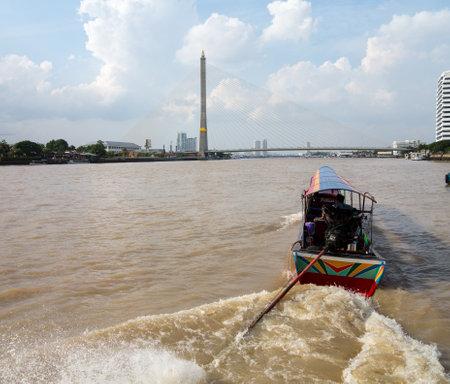 BANGKOK, THAILAND - JUNE 23: Boat on Chao Phraya River by Rama VIII bridge on June 23, 2012. The bridge is 2.45km long.