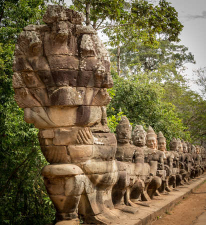 South gate to angkor thom in Cambodia is lined with warriors and demons photo