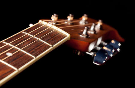 acoustical: Macro shot down the fretboard of acoustic guitar with shallow depth of field